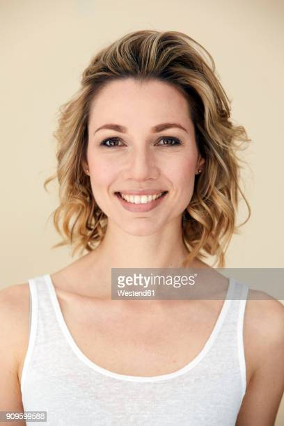 Portrait of blond woman wearing tank top, smiling