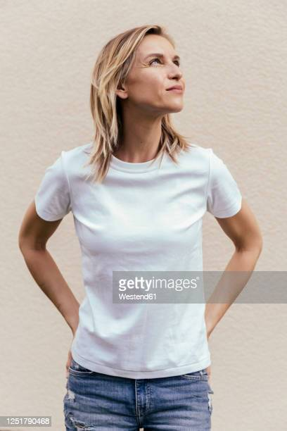 portrait of blond woman wearing white t-shirt in front of light wall looking up - europäischer abstammung stock-fotos und bilder