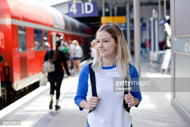 Portrait of blond woman with backpack on platform