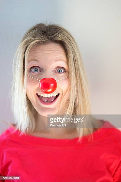 portrait of blond woman with clown's nose - clown's nose stock photos and pictures