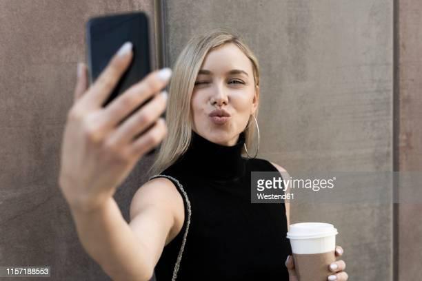portrait of blond woman with coffee to go taking selfie with smartphone - kussmund stock-fotos und bilder