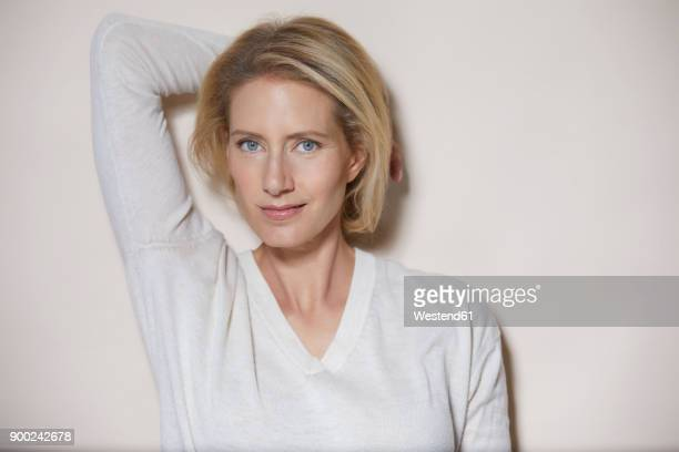 Portrait of blond woman with hand behind her head in front of light background
