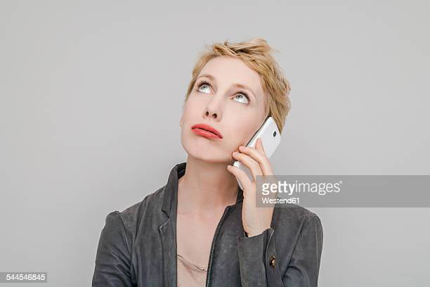 portrait of blond woman with smartphone pouting mouth looking up - mujeres de mediana edad fotografías e imágenes de stock