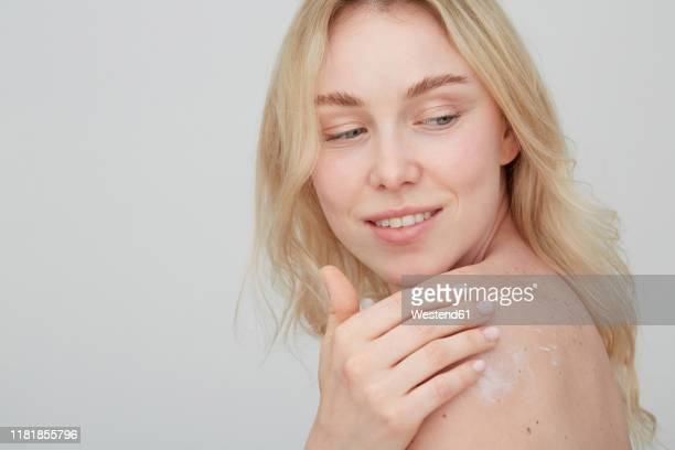 Young Woman Lying On Bed Resting Chin On Hands Portrait