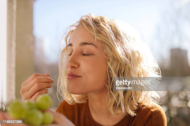 portrait of blond young woman eating green grapes - vergnügen stock-fotos und bilder