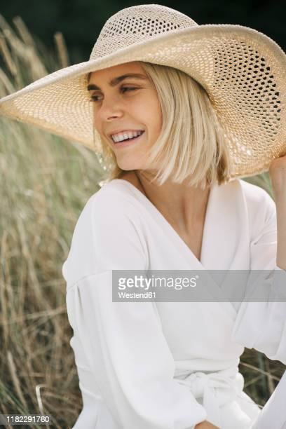 portrait of blond young woman in dunes wearing white wrap blouse and summer hat - blouse stockfoto's en -beelden