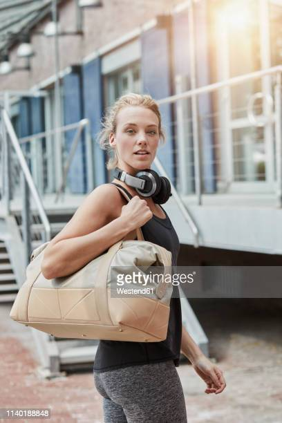 portrait of blond young woman with headphones and sports bag in front of gym - スポーツバッグ ストックフォトと画像