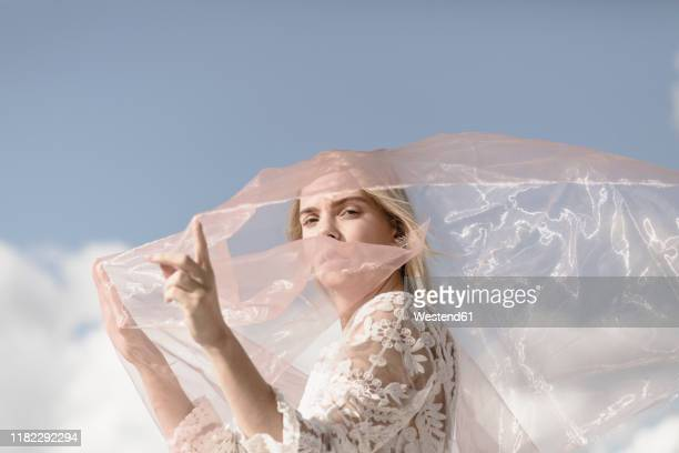 portrait of blond young woman with veil against sky - lace textile stock pictures, royalty-free photos & images