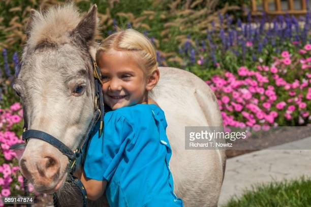 Portrait of blonde Amish girl and pony
