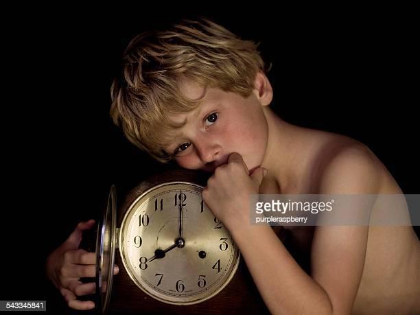 Portrait of blonde boy (6-7) with antique clock