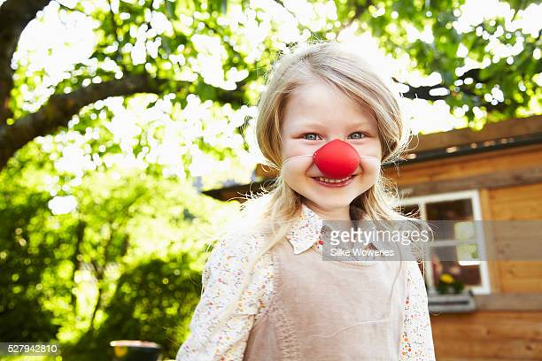 Portrait of blonde girl (6-7) dressed up as clown with red nose