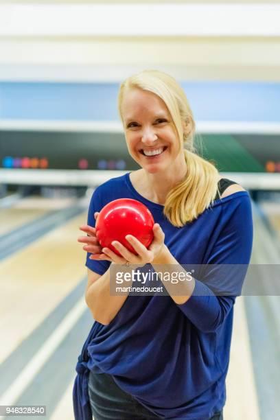 Porträt von blonde Reife Frau Bowling zu spielen.
