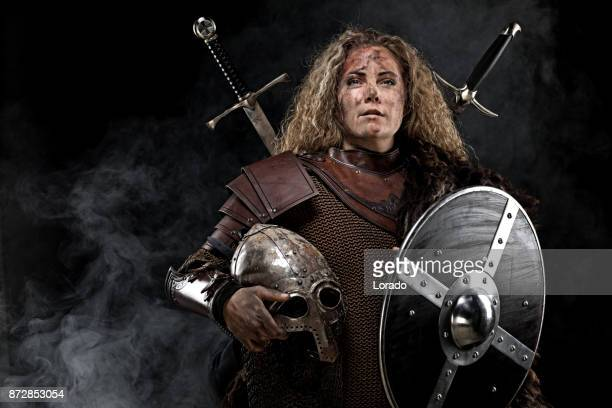 Portrait of blonde viking warrior female holding a sword in studio shot
