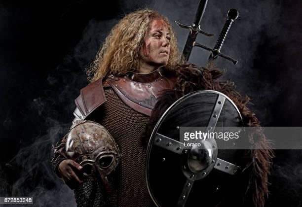 Portrait of blonde viking warrior female holding a sword in studio shot