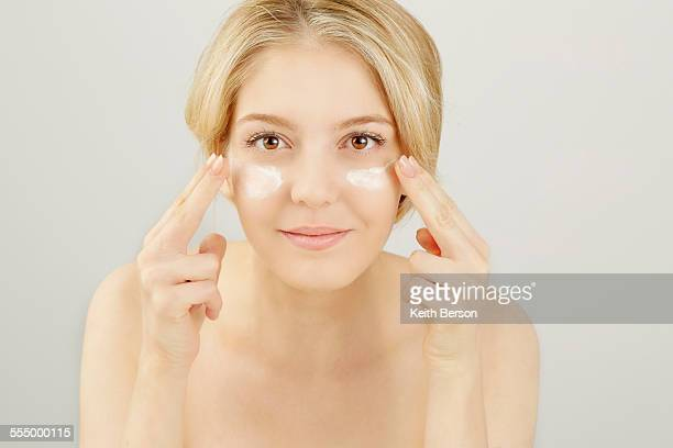 Portrait of blonde woman applying face cream