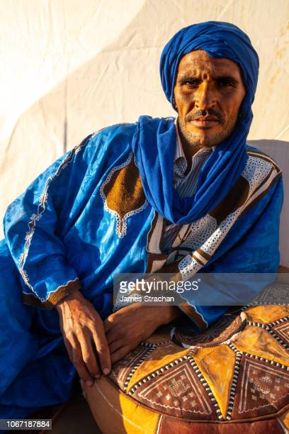 portrait of blue man (tuareg) in traditional dress from the desert resting on a brown leather stitched pouffe, erg chebbi, near merzouga, morocco (model release) - touareg photos et images de collection