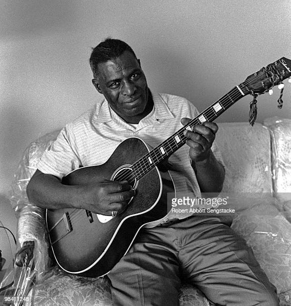 Portrait of blues musician Chester Arthur Burnett better known as Howlin' Wolf posing with his guitar during an interview for the Chicago Defender...