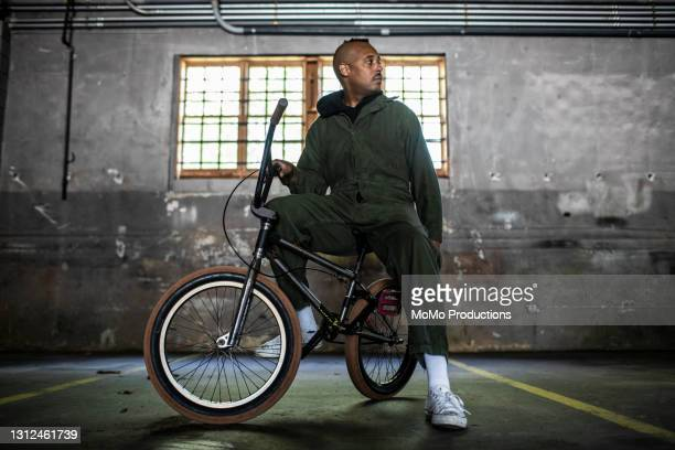 portrait of bmx rider in warehouse environment - african american culture stock pictures, royalty-free photos & images
