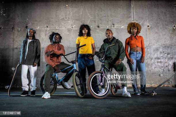 portrait of bmx riders and skateboarders in warehouse environment - vintage lesbian photos stock pictures, royalty-free photos & images