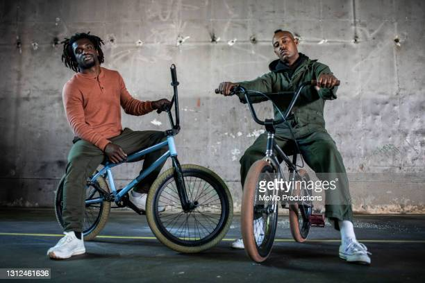 portrait of bmx riders in warehouse environment - black trousers stock pictures, royalty-free photos & images