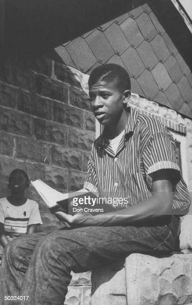 Portrait of Bobby Cain a student at the recently desegregated Clinton High School as he sits outside with an open school book in his hands Clinton...