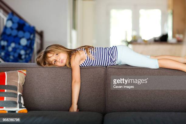 portrait of bored girl lying on sofa at home - boredom stock pictures, royalty-free photos & images