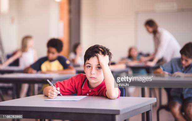 portrait of bored schoolboy in classroom - attending stock pictures, royalty-free photos & images