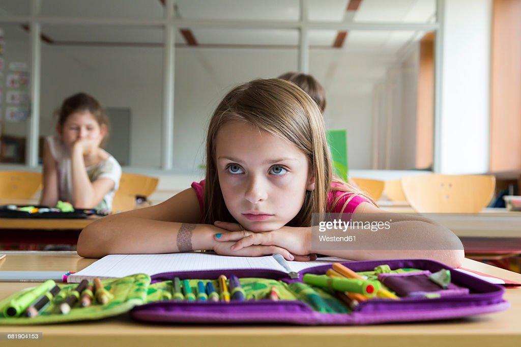 Portrait of bored schoolgirl at class : Stock Photo