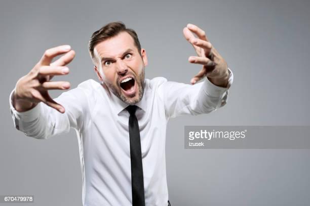 portrait of bossy businessman shouting, studio shot - izusek imagens e fotografias de stock