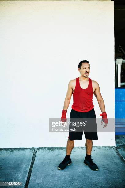 portrait of boxer standing against wall after workout in boxing gym - boxing shorts stock pictures, royalty-free photos & images
