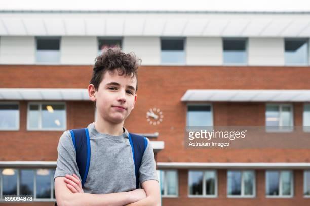 Portrait of boy (12-13 in front of school building