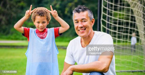 portrait of boy and coach on soccer field - football league stock pictures, royalty-free photos & images