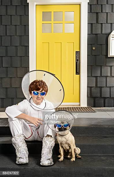 Portrait of boy (13-15) and dog wearing protective collar