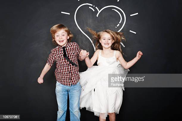 Portrait of boy and girl jumping