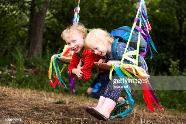 portrait of boy and his little sister having fun with a swing - children only stock pictures, royalty-free photos & images