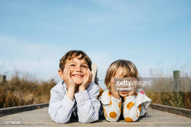 portrait of boy and his little sister lying side by side on boardwalk pulling funny faces - nur kinder stock-fotos und bilder