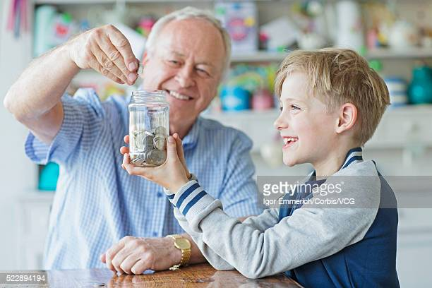 Portrait of boy ( 8-9) and senior man putting savings in glass jar