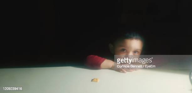 portrait of boy at table against black background - one boy only stock pictures, royalty-free photos & images