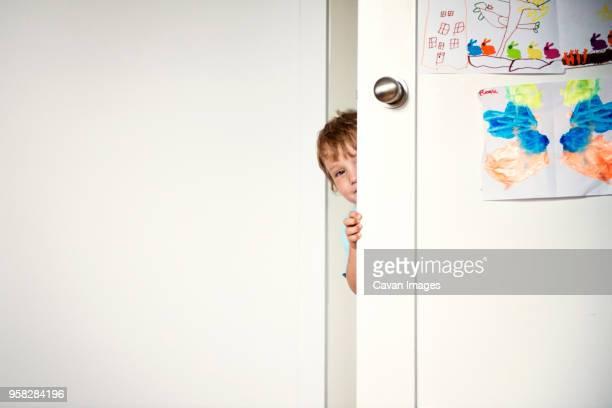 portrait of boy behind door at home - 隠れる ストックフォトと画像