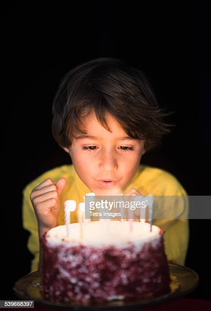 Portrait of boy (6-7) blowing out birthday candles