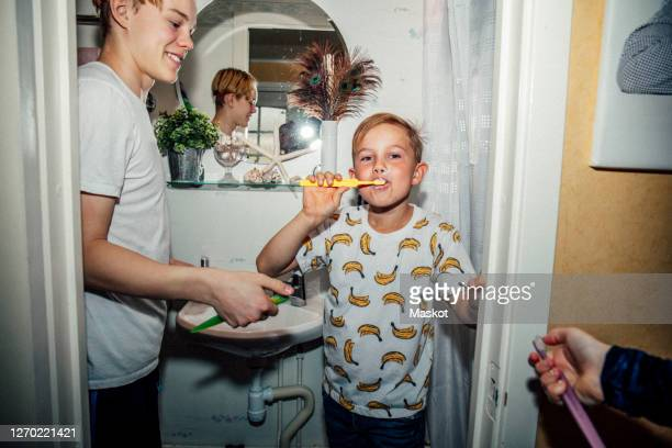 portrait of boy brushing teeth near bathroom sink - sweden stock pictures, royalty-free photos & images