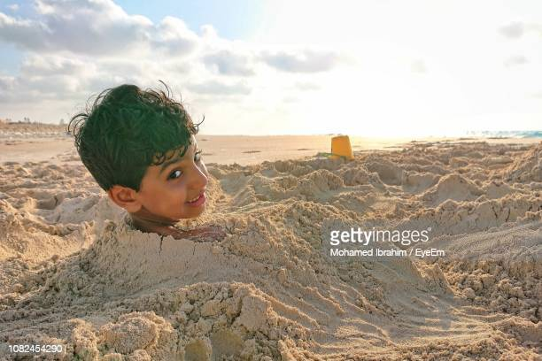 portrait of boy buried in sand on beach against sky - buried stock pictures, royalty-free photos & images