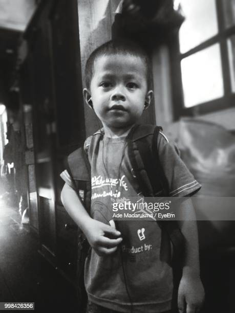 Portrait Of Boy Carrying Backpack While Listening Music On In-Ear Headphones At Home