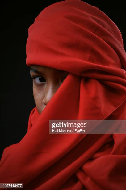 portrait of boy covering face with red textile against black background - heri mardinal stock pictures, royalty-free photos & images