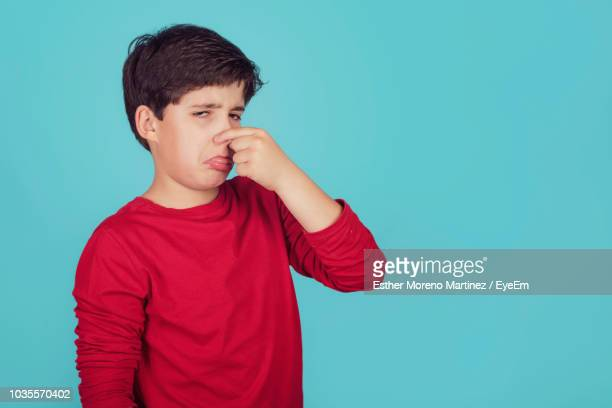 Portrait Of Boy Covering Nose Against Blue Background