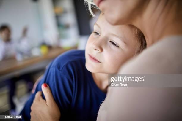 portrait of boy cuddling with mother at home - 8 9 años fotografías e imágenes de stock
