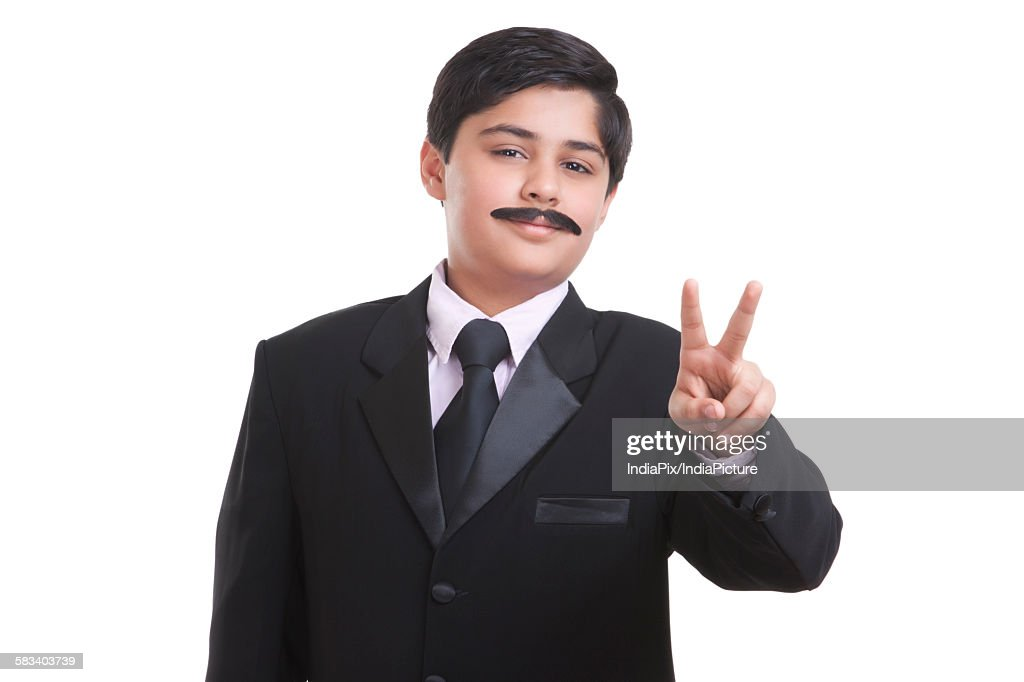 Portrait of boy dressed as businessman giving peace sign : Stock Photo