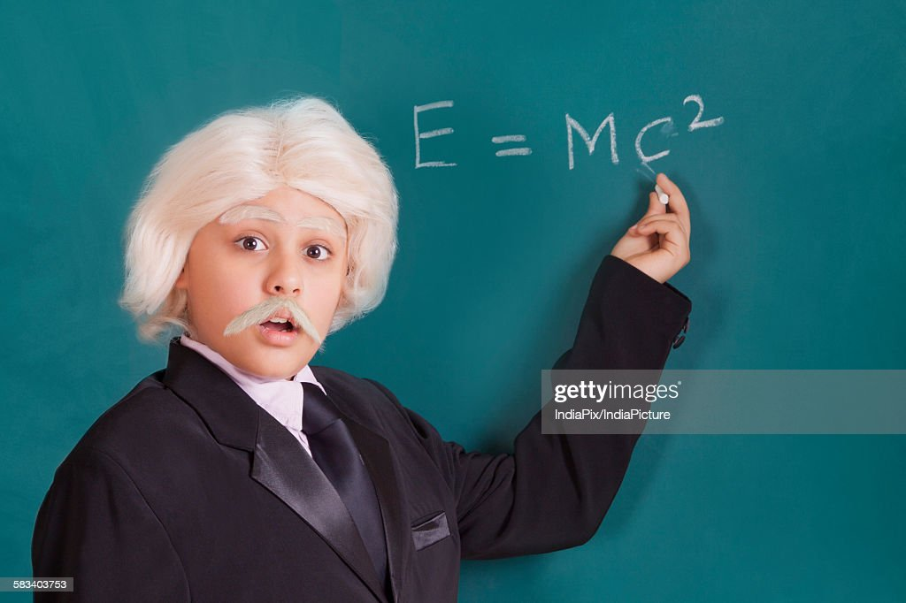 Portrait of boy dressed as Einstein with maths equation : Stock Photo