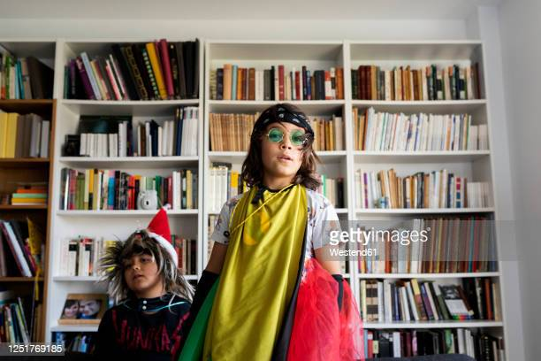 portrait of boy dressed up as a rock star in the living room with his younger brother - musicien pop photos et images de collection