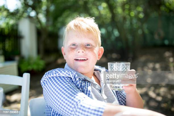 Portrait of boy drinking glass of water outdoors